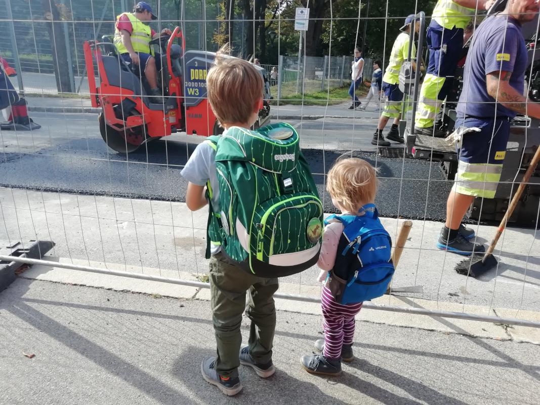 Kinder betrachten eine Straßenbaustelle