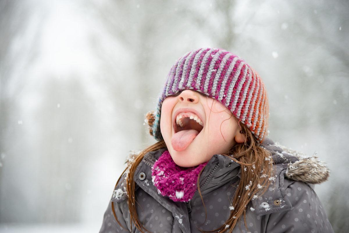 Fröhliches Mädchen will Schneeflocken fangen